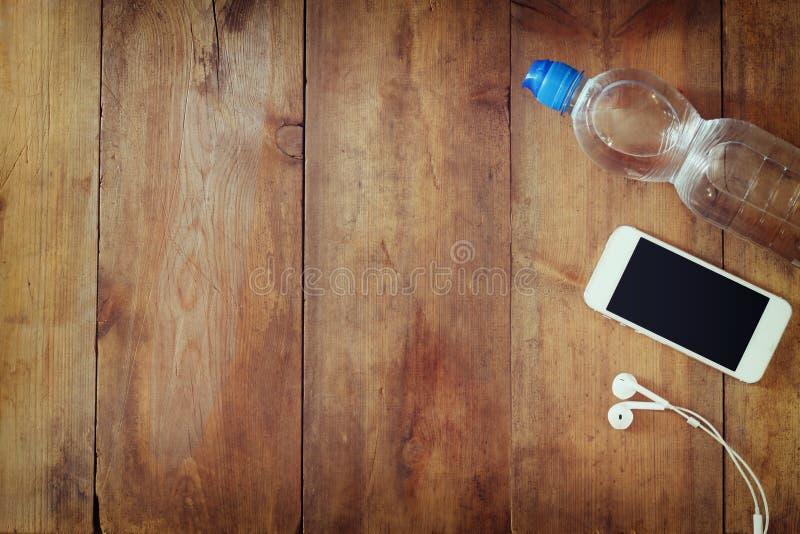 Έννοια ικανότητας με το μπουκάλι νερό, κινητό τηλέφωνο με τα ακουστικά πέρα από το ξύλινο υπόβαθρο Φιλτραρισμένη εικόνα στοκ φωτογραφίες