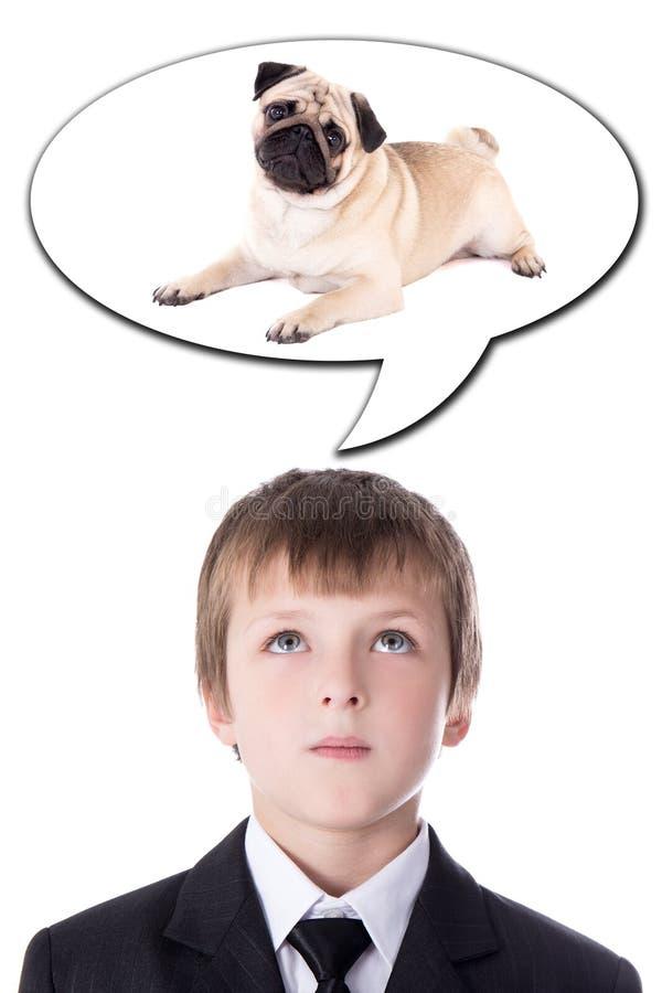 Έννοια ιδέας - το μικρό παιδί στο επιχειρησιακό κοστούμι που σκέφτεται για το σκυλί είναι στοκ εικόνα