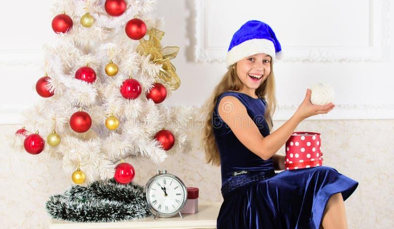 έννοια καλή χρονιά Το παιδί γιορτάζει τα Χριστούγεννα στο σπίτι Το κορίτσι παιδιών κάθεται κοντά στο κιβώτιο δώρων λαβής χριστουγ στοκ φωτογραφίες με δικαίωμα ελεύθερης χρήσης