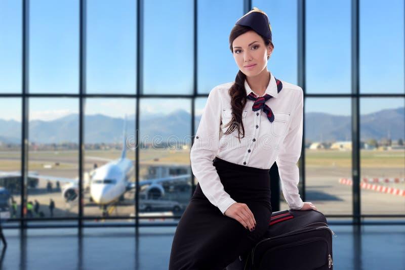 Έννοια καλοκαιριού, διακοπών και ταξιδιού - αεροσυνοδός με τη βαλίτσα στον αερολιμένα στοκ εικόνες