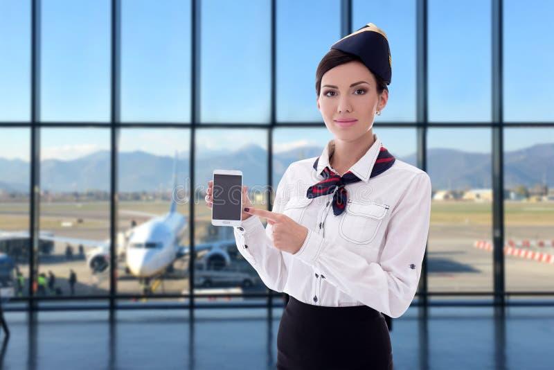 Έννοια καλοκαιριού, διακοπών και ταξιδιού - αεροσυνοδός που κρατά το έξυπνο τηλέφωνο με την κενή οθόνη στον αερολιμένα στοκ φωτογραφία