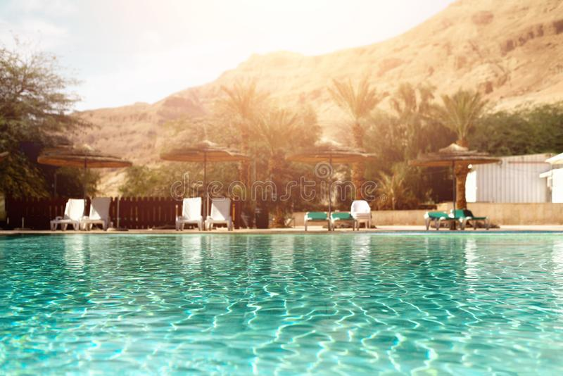 Έννοια καλοκαιριού, ταξιδιού, διακοπών και διακοπών Το σαλόνι προεδρεύει κοντά στην πισίνα ενάντια στην έρημο Judean Τυρκουάζ λίμ στοκ εικόνες