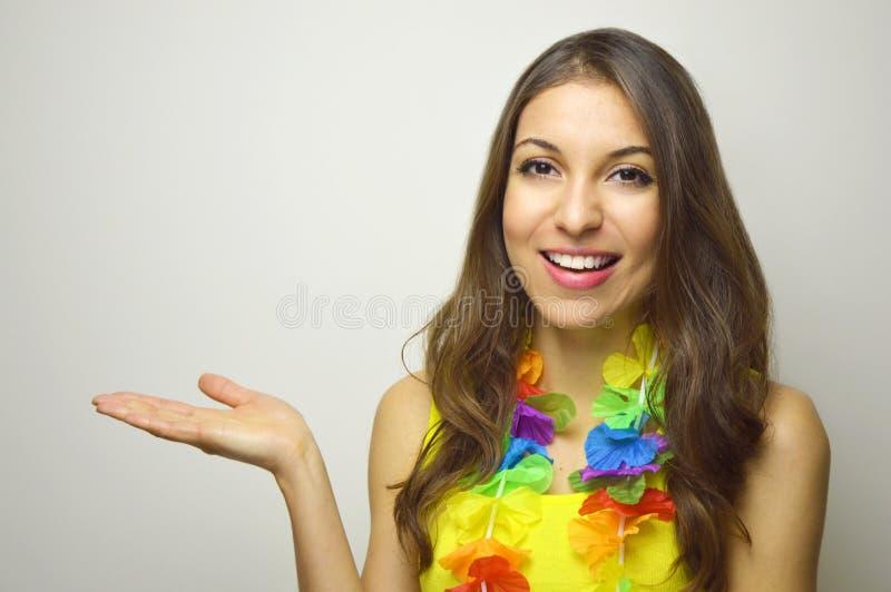 έννοια καρναβαλιού Όμορφη εύθυμη νέα γυναίκα έτοιμη για το κόμμα καρναβαλιού που παρουσιάζει το προϊόν ή κείμενό σας στο γκρίζο υ στοκ φωτογραφία