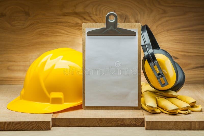Έννοια κατασκευής ασφάλεια της εργασίας κενό φύλλο εγγράφου στα κίτρινα ακουστικά γαντιών δέρματος κρανών περιοχών αποκομμάτων στοκ εικόνα