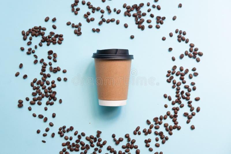 Έννοια καφέ Φασόλια καφέ με το φλυτζάνι εγγράφου στο μπλε υπόβαθρο στοκ φωτογραφία