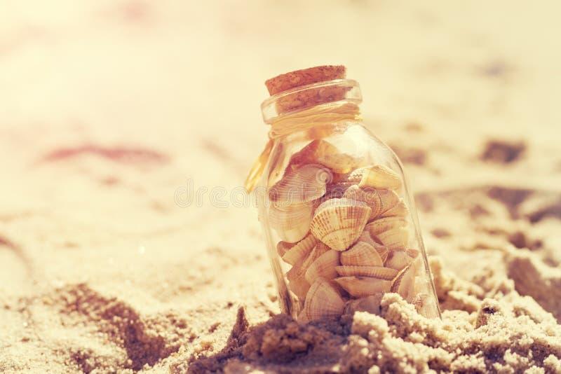 Έννοια καλοκαιριού ή διακοπών Θαλασσινά κοχύλια στα μπουκάλια στην άμμο τονισμός στοκ εικόνες με δικαίωμα ελεύθερης χρήσης