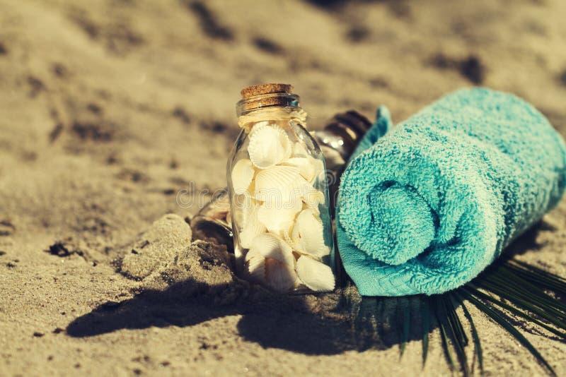 Έννοια καλοκαιριού ή διακοπών Θαλασσινά κοχύλια στα μπουκάλια στην άμμο με το BL στοκ εικόνα με δικαίωμα ελεύθερης χρήσης