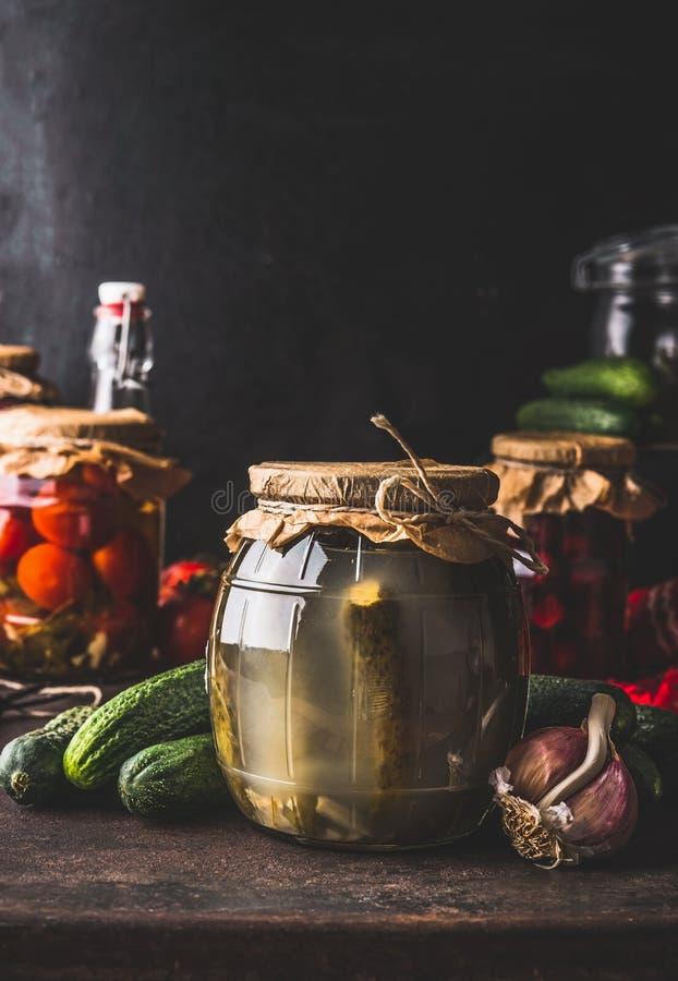 Έννοια κονσερβών συγκομιδών Βάζο γυαλιού με το ζυμωνομμένο παστωμένο αγγούρι στο σκοτεινό αγροτικό πίνακα κουζινών με άλλη κονσέρ στοκ φωτογραφίες με δικαίωμα ελεύθερης χρήσης