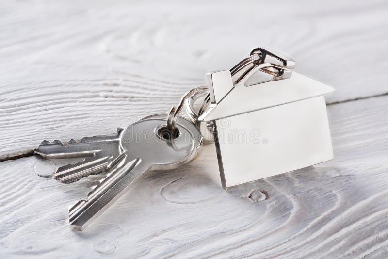 Έννοια κτημάτων, keychain με το σύμβολο σπιτιών, κλειδί στο ελαφρύ ξύλο στοκ εικόνα με δικαίωμα ελεύθερης χρήσης