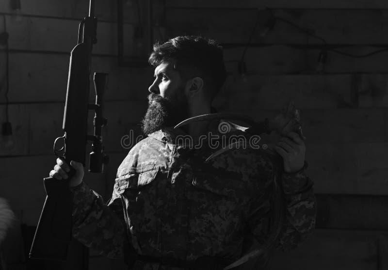 Έννοια κυνηγών Το πορτρέτο του γενειοφόρου σύγχρονου κυνηγού με το τρόπαιό του κρατά το τουφέκι Το άτομο με τη γενειάδα φορά τον  στοκ εικόνα με δικαίωμα ελεύθερης χρήσης