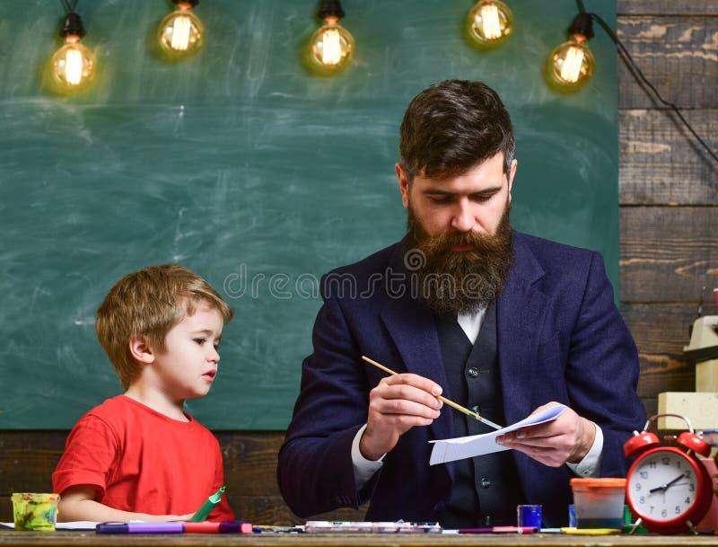 Έννοια μαθήματος τεχνών Δάσκαλος με τη γενειάδα, σχέδιο πατέρων ενώ λίγος γιος κρεμά έξω κοντά, στην τάξη, στον πίνακα κιμωλίας ε στοκ εικόνες με δικαίωμα ελεύθερης χρήσης