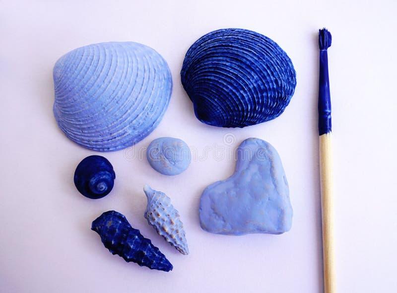 Έννοια μνημών θερινών διακοπών Κοχύλια και χαλίκια που χρωματίζονται στο ελαφρύ και σκούρο μπλε χρώμα και τη βούρτσα με το μπλε χ στοκ εικόνες