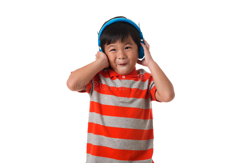 έννοια μουσικής και τεχνολογίας Ασιατικό μικρό παιδί με το ακουστικό στοκ φωτογραφία