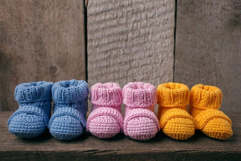 Έννοια μωρών: διαφορετικές χρωματισμένες λείες μωρών, τρία ζευγάρια των λειών μωρών σε ένα ξύλινο υπόβαθρο στοκ φωτογραφία με δικαίωμα ελεύθερης χρήσης