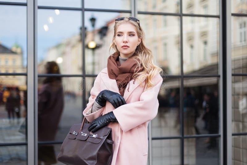 Έννοια μόδας οδών: πορτρέτο της νέας όμορφης γυναίκας που φορά το ρόδινο παλτό με την τοποθέτηση τσαντών στην πόρτα γυαλιού Πόλη στοκ φωτογραφίες