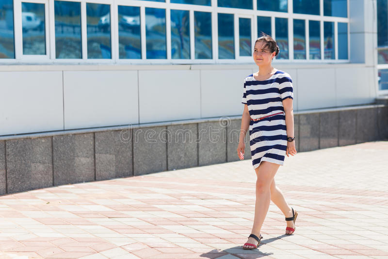 Έννοια μόδας οδών όμορφες νεολαίες γυνα&iota Όμορφο κορίτσι που φορά το ριγωτό φόρεμα που περπατά στην οδό στοκ φωτογραφία με δικαίωμα ελεύθερης χρήσης