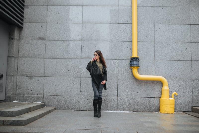 Έννοια μόδας: όμορφο νέο κορίτσι με μακρυμάλλη, τα γυαλιά, κόκκινα χείλια που στέκεται κοντά στο σύγχρονο τοίχο που φορά στο πράσ στοκ εικόνες