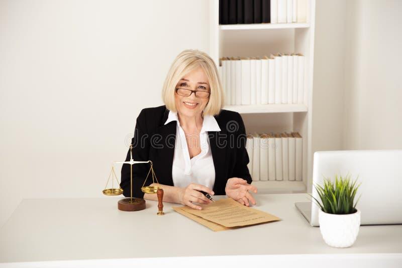 Έννοια νόμου Η γυναίκα στα γυαλιά που λειτουργούν με το έγγραφο στοκ φωτογραφία