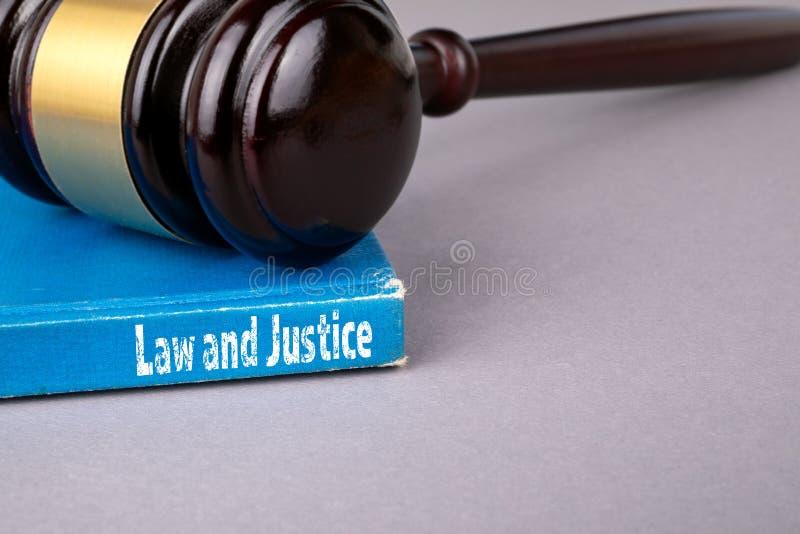Έννοια νόμου και δικαιοσύνης μπλε βιβλίο σε έναν γκρίζο πίνακα γραφείων στοκ φωτογραφία