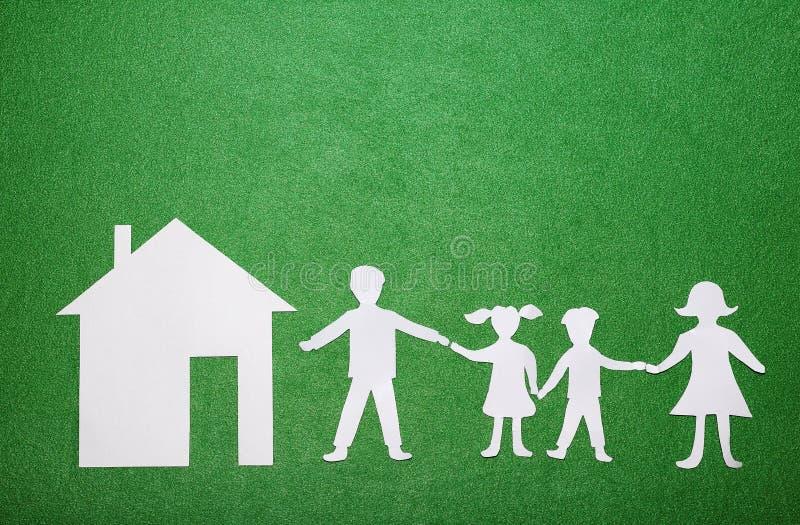 Έννοια οικογένειας και σπιτιών Γονείς και παιδιά που κρατούν τα χέρια Οικογενειακοί αριθμοί και σπίτι εγγράφου στο πράσινο της υφ στοκ φωτογραφία με δικαίωμα ελεύθερης χρήσης