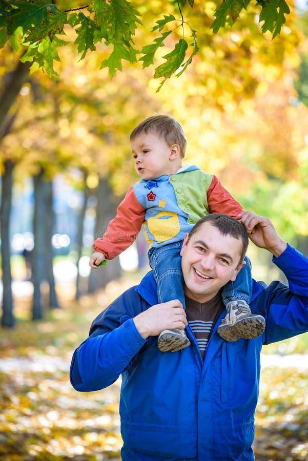 Έννοια οικογένειας, παιδικής ηλικίας και πατρότητας ευτυχής φέρνοντας γιος πατέρων με τα φύλλα σφενδάμου πέρα από το υπόβαθρο πάρ στοκ φωτογραφίες