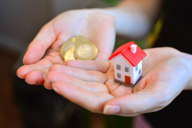 Έννοια οικογενειακών κατοικιών Μικροσκοπικά σπίτι και νομίσματα στα θηλυκά χέρια στοκ εικόνες με δικαίωμα ελεύθερης χρήσης