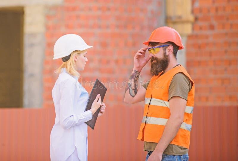 Έννοια Οικοδομικής Βιομηχανίας Ο μηχανικός γυναικών και ο γενειοφόρος βάναυσος οικοδόμος συζητούν την πρόοδο κατασκευής Σχέσεις στοκ φωτογραφία
