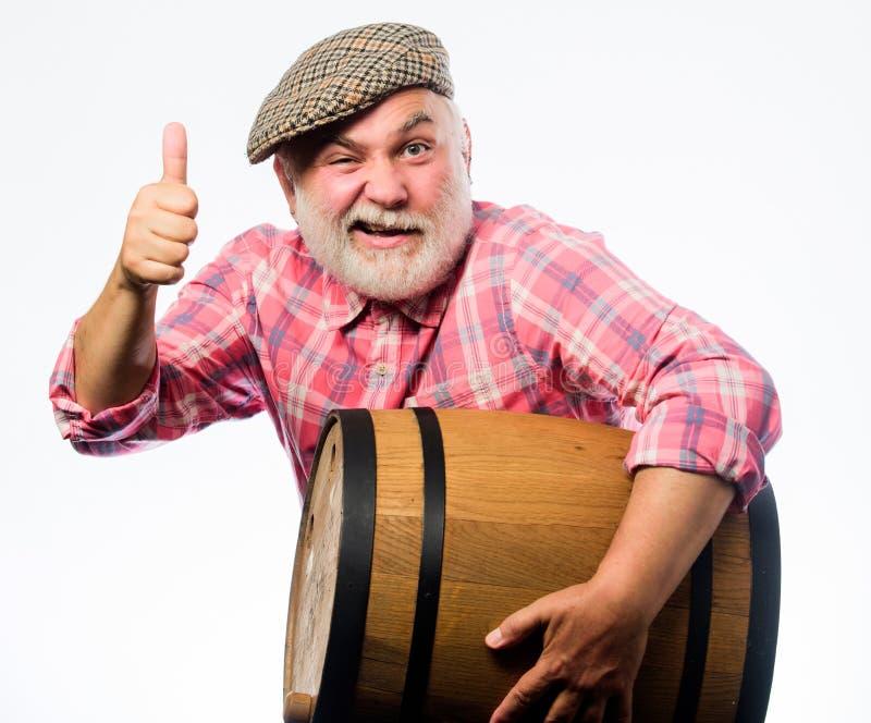 Έννοια οινοποιιών Σπιτικό κρασί Παραγωγή της οικογενειακής παράδοσης κρασιού Ο γενειοφόρος πρεσβύτερος ατόμων φέρνει το ξύλινο βα στοκ φωτογραφία