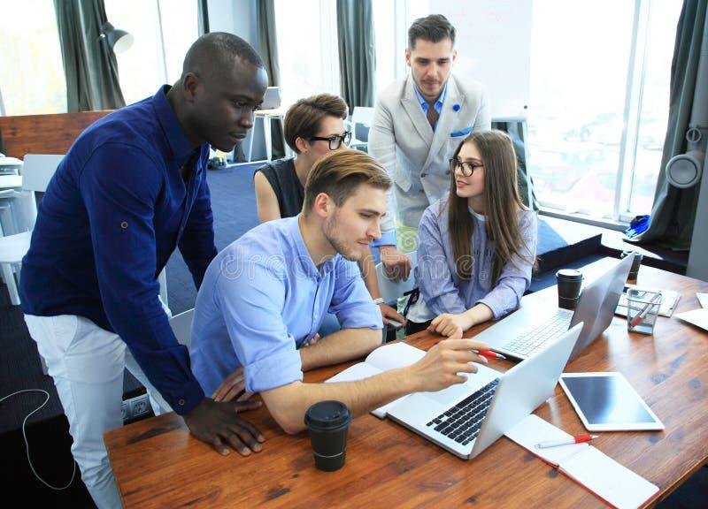 Έννοια ομαδικής εργασίας Νέοι δημιουργικοί συνάδελφοι που εργάζονται με το νέο πρόγραμμα ξεκινήματος στο σύγχρονο γραφείο Η ομάδα στοκ εικόνες