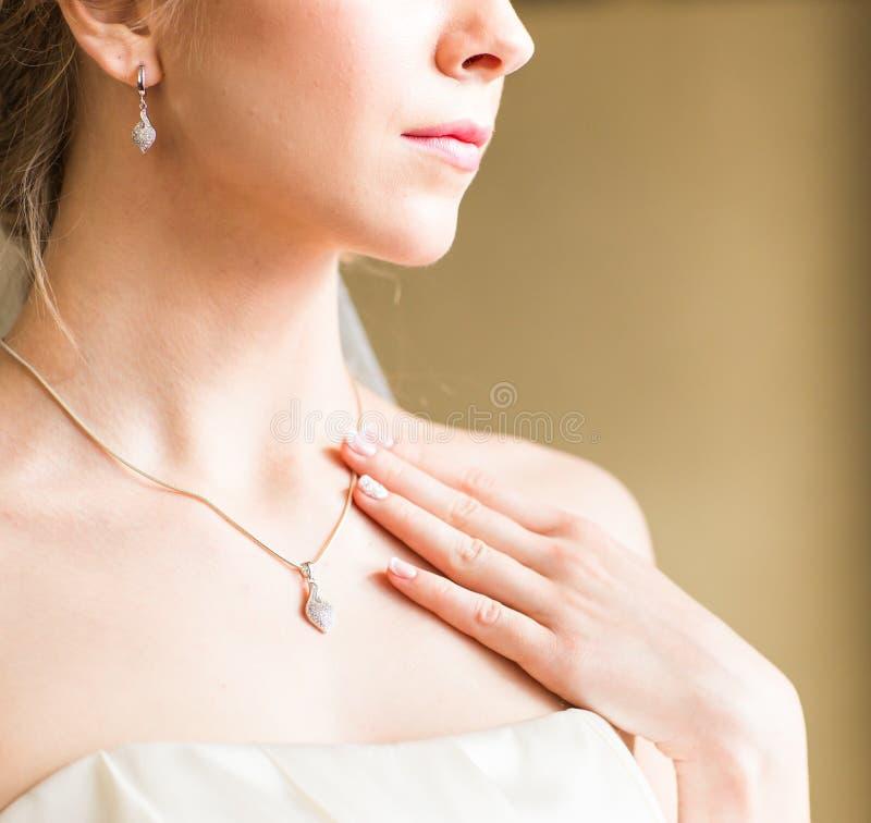 Έννοια ομορφιάς και κοσμήματος - γυναίκα που φορά το λαμπρό κρεμαστό κόσμημα διαμαντιών στοκ φωτογραφία