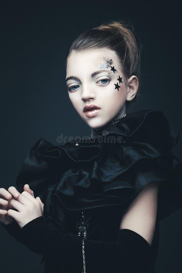 Έννοια ομορφιάς και μόδας: Μικρό κορίτσι που φορά τη μαύρη εξάρτηση δημιουργικός αποτελέστ στοκ εικόνα με δικαίωμα ελεύθερης χρήσης