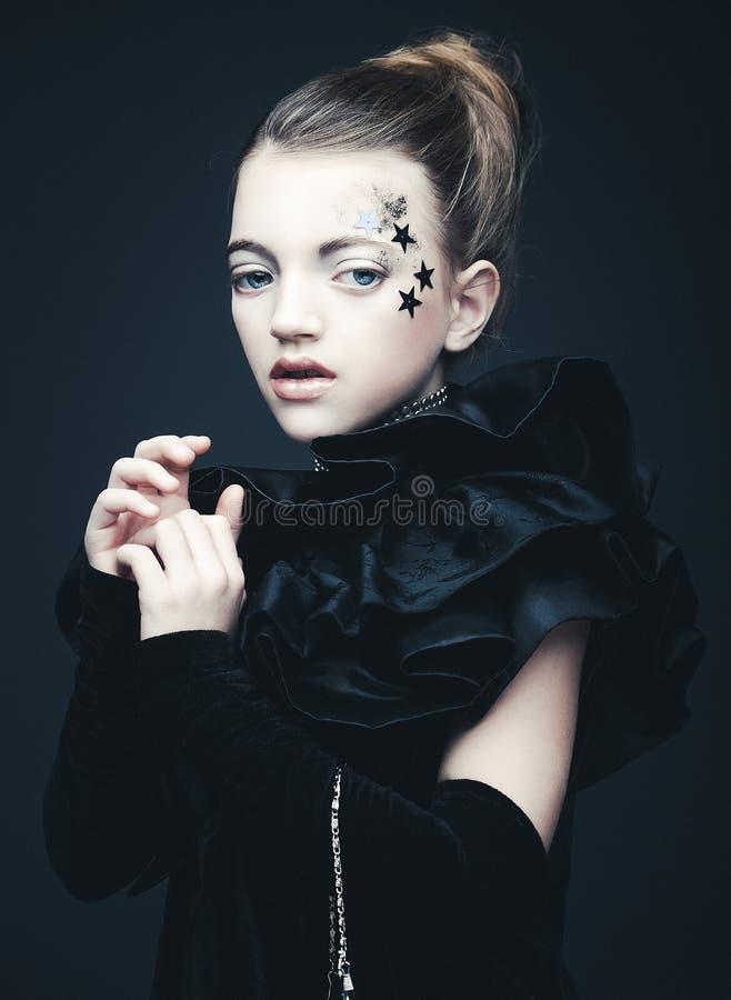 Έννοια ομορφιάς και μόδας: Μικρό κορίτσι που φορά τη μαύρη εξάρτηση δημιουργικός αποτελέστ στοκ εικόνες