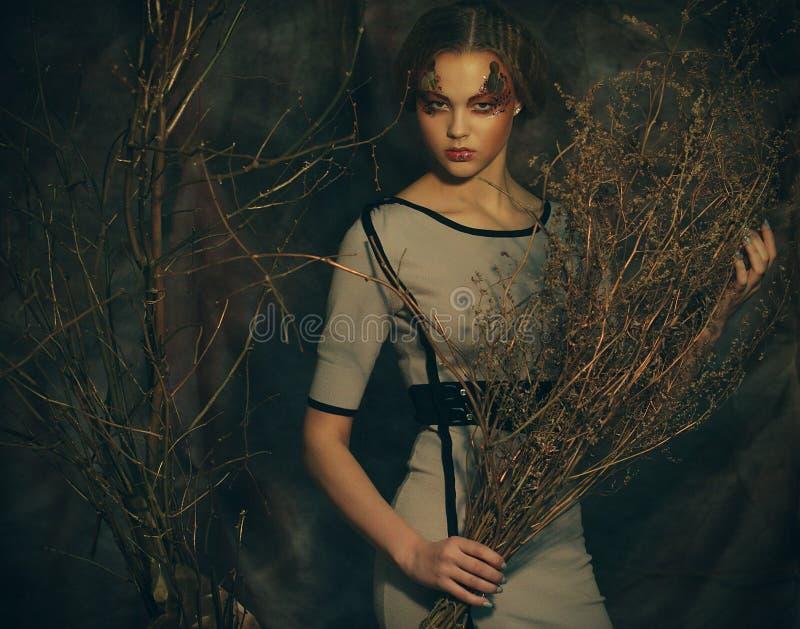 Έννοια ομορφιάς και τέχνης: η γυναίκα με φωτεινό αποτελεί με τους ξηρούς κλάδους, βλαστός στούντιο στοκ εικόνες με δικαίωμα ελεύθερης χρήσης