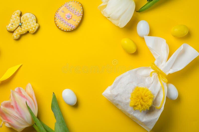 Έννοια Πάσχας - διαμορφωμένη λαγουδάκι τσάντα με τα αυγά και τα λουλούδια στο φωτεινό κίτρινο υπόβαθρο, στοκ φωτογραφία με δικαίωμα ελεύθερης χρήσης