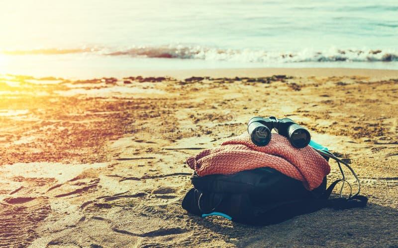 Έννοια περιπέτειας ταξιδιού Οι διόπτρες και το σακίδιο πλάτης πεζοπορίας βρίσκονται στην ακτή ηλιοφάνειας στοκ εικόνα