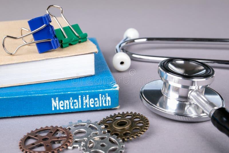 Έννοια πνευματικών υγειών μπλε βιβλίο σε έναν γκρίζο πίνακα γραφείων στοκ φωτογραφία