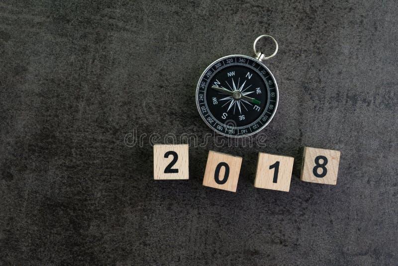 Έννοια πρόβλεψης ή κατεύθυνσης έτους 2018 με την πυξίδα και woode στοκ φωτογραφία