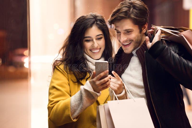 Έννοια πώλησης και καταναλωτισμού Ζεύγος με τις τσάντες και το smartphone αγορών στοκ εικόνες