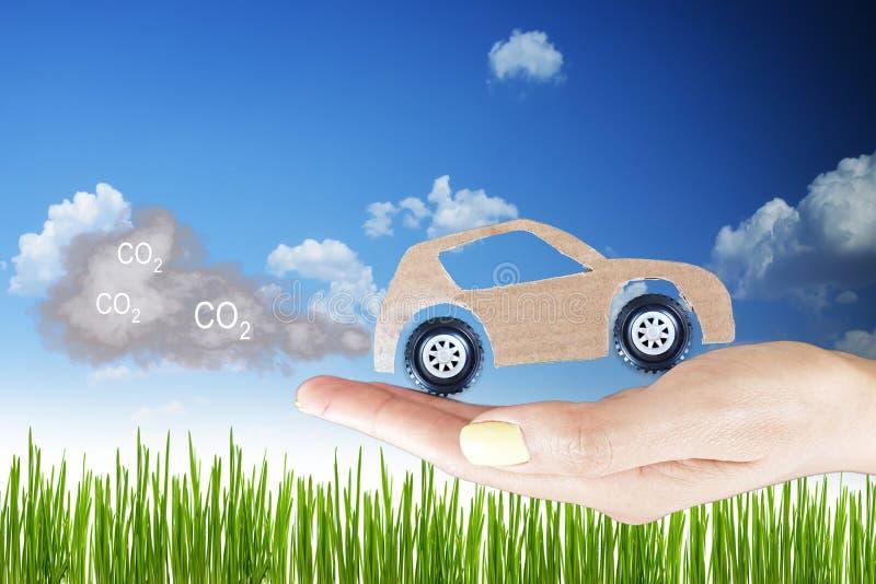 Έννοια ρύπανσης, αυτοκίνητο χαρτονιού με τα αέρια εξάτμισης στο χέρι γυναικών ενάντια στον πράσινο τομέα χλόης στοκ εικόνες