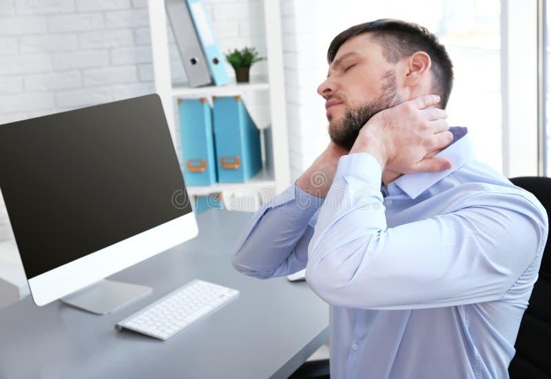 Έννοια στάσης Άτομο που πάσχει από τον πόνο λαιμών εργαζόμενο με τον υπολογιστή στο γραφείο στοκ φωτογραφία