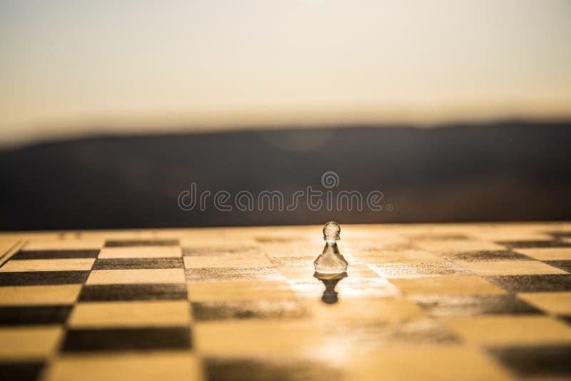 Έννοια στρατηγικής και τακτικής Παγωμένοι παγωμένοι αριθμοί σκακιού που στέκονται σε μια σκακιέρα κατά τη διάρκεια του ηλιοβασιλέ στοκ φωτογραφίες