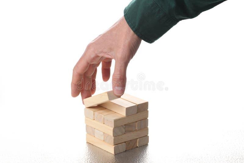 Έννοια στρατηγικής προγραμματισμού: το ανθρώπινο χέρι κινεί έναν ξύλι στοκ εικόνα