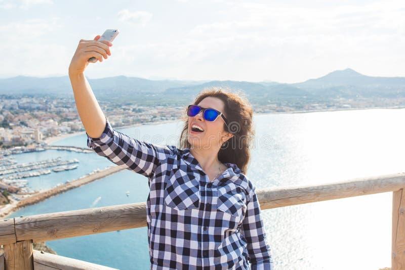 Έννοια ταξιδιού, διακοπών και διακοπών - νέα γυναίκα που έχει τη διασκέδαση, που παίρνουν selfie, το τρελλά συναισθηματικά πρόσωπ στοκ φωτογραφίες
