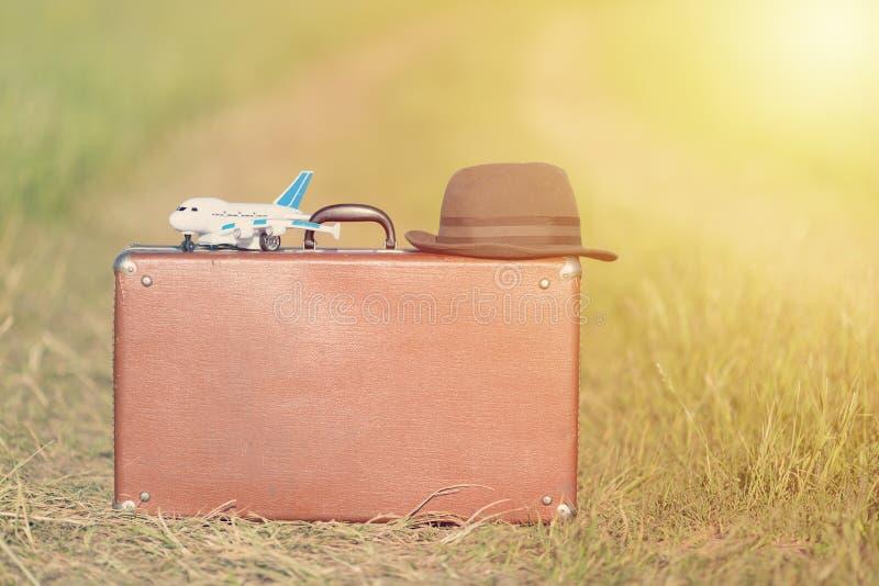Έννοια ταξιδιού και περιπέτειας Εκλεκτής ποιότητας καφετιά βαλίτσα και καπέλο με το αεροπλάνο παιχνιδιών κοντά στο δρόμο στον πρά στοκ φωτογραφίες