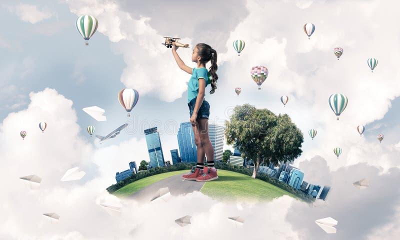 Έννοια της απρόσεκτης ευτυχούς παιδικής ηλικίας με να ονειρευτεί κοριτσιών για να γίνει πειραματικός στοκ φωτογραφία