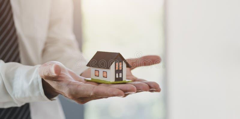 Έννοια της ασφάλισης ακινήτων: ασφαλιστής που κρατά μοντέλο σπιτιού στο χέρι του στοκ φωτογραφία με δικαίωμα ελεύθερης χρήσης