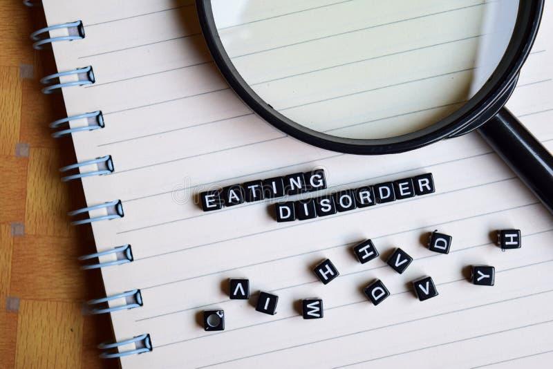 Έννοια της διατροφικής διαταραχής στους ξύλινους κύβους με τα βιβλία στο υπόβαθρο στοκ φωτογραφία