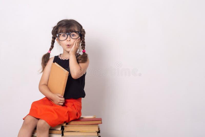 Έννοια της εκπαίδευσης και της ανάγνωσης Εργατικό παιδί Μικρό κορίτσι που διαβάζει το βιβλίο στοκ εικόνες