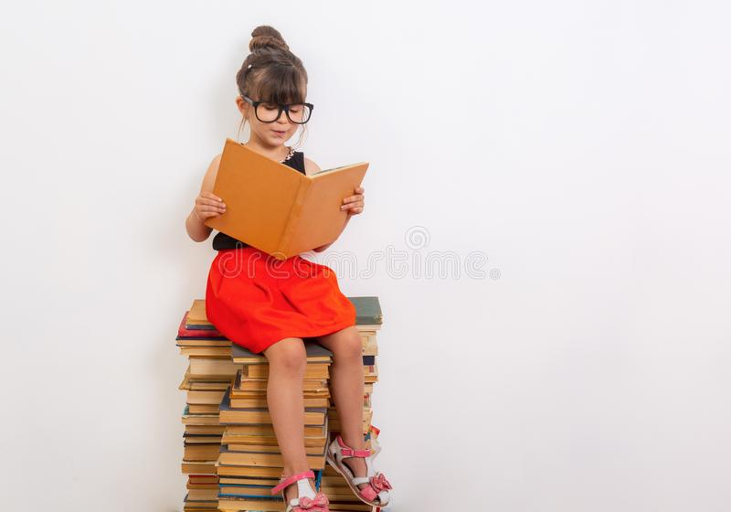 Έννοια της εκπαίδευσης και της ανάγνωσης Εργατικό παιδί Μικρό κορίτσι που διαβάζει το βιβλίο στοκ φωτογραφία