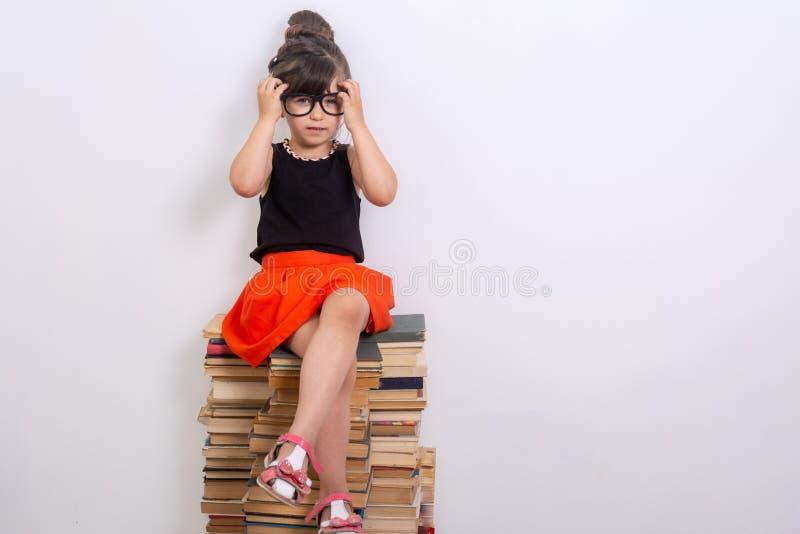 Έννοια της εκπαίδευσης και της ανάγνωσης Εργατικό παιδί Μικρό κορίτσι που διαβάζει το βιβλίο στοκ φωτογραφίες